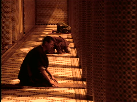 vídeos de stock, filmes e b-roll de dolly shot profile three middle eastern men on hands + knees praying by columns of mosque / morocco - ajoelhando se