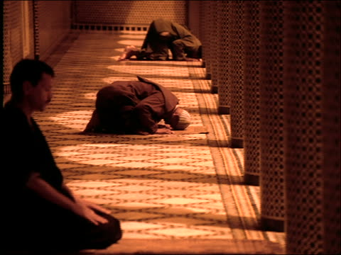 dolly shot PROFILE three Middle Eastern men on hands + knees praying by columns of mosque / Morocco