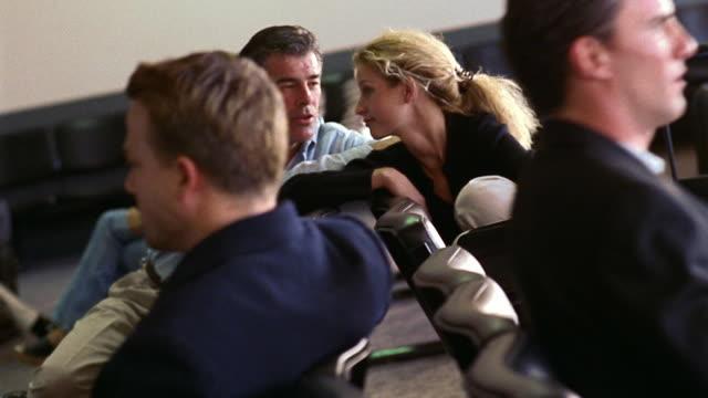 vídeos y material grabado en eventos de stock de canted dolly shot pan rack focus travelers sitting in phoenix sky harbor airport waiting area / arizona - encuadre de tres cuartos