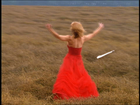 dolly shot rear view blond woman in formal red dress with arms raised singing + bowing in grassy field - bowing stock videos & royalty-free footage