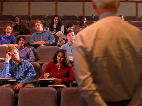 dolly shot REAR VIEW PAN male professor talking to students in lecture hall / Boston, MA