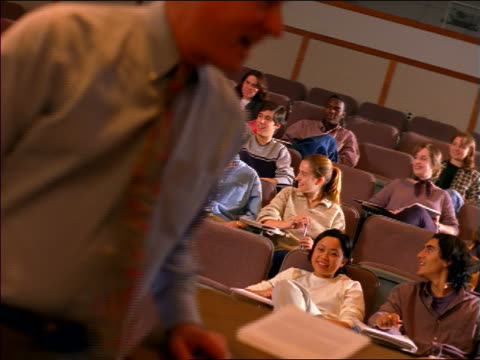 dolly shot rear view pan male professor talking to students in lecture hall / boston, ma - lecture hall bildbanksvideor och videomaterial från bakom kulisserna