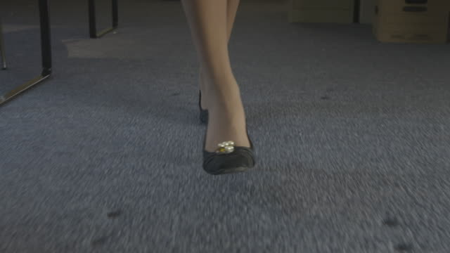 dolly shot of the feet of a woman walking in an office - カーペット点の映像素材/bロール