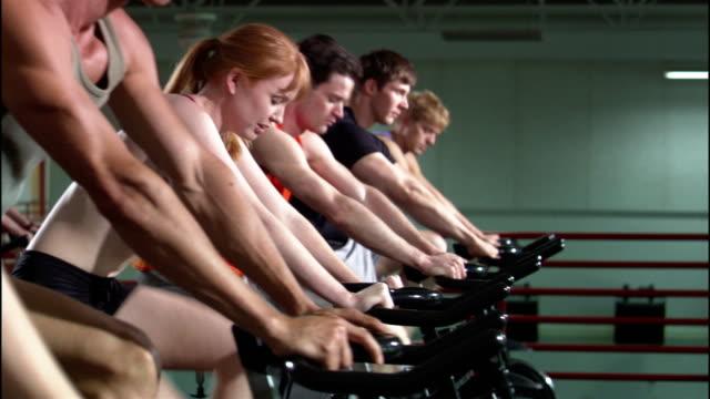 vídeos y material grabado en eventos de stock de dolly shot row of men and women riding stationary bikes in exercise class - bicicleta estática