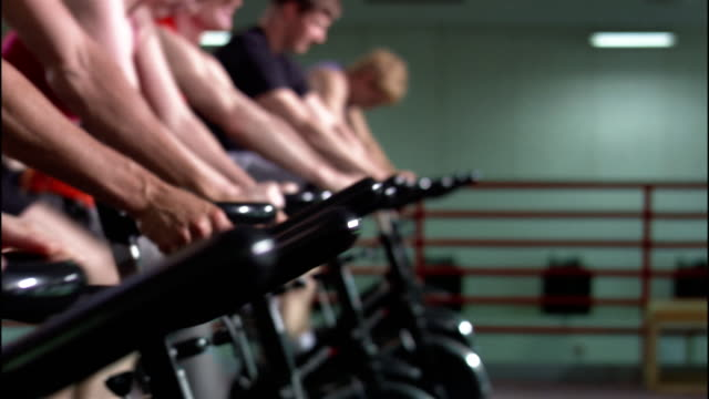 Dolly shot row of men riding stationary bikes in exercise class