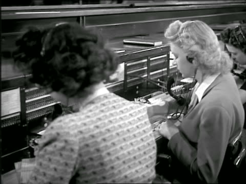b/w 1946 dolly shot row of women wearing headseats sitting at busy switchboard - 電話交換機点の映像素材/bロール