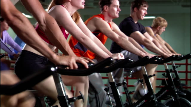 dolly shot rows of men and women riding stationary bikes in exercise class - fitnesskurs stock-videos und b-roll-filmmaterial