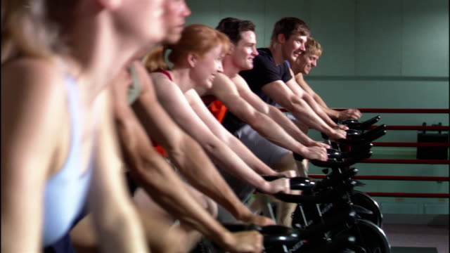 dolly shot rows of men and women riding stationary bikes in exercise class / standing up and pedalling - fitnesskurs stock-videos und b-roll-filmmaterial