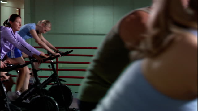 Dolly shot rows of men and women riding stationary bikes in exercise class / standing up and pedalling
