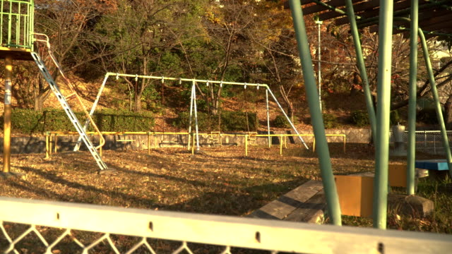 dolly shot : rusted playground in morning