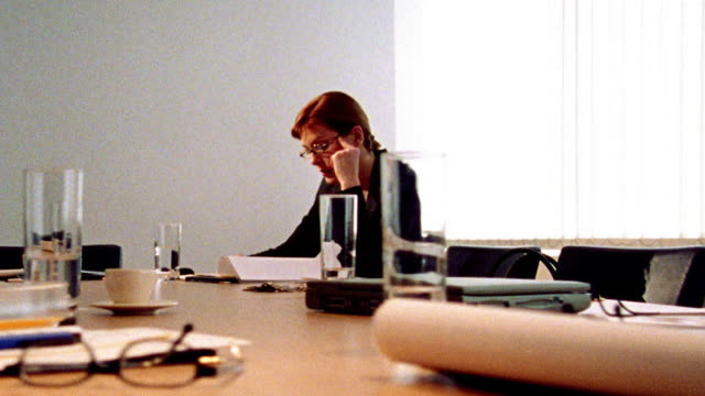 vídeos de stock e filmes b-roll de dolly shot selective focus zoom in businesswoman looking stressed alone at table in conference room after meeting - super exposto