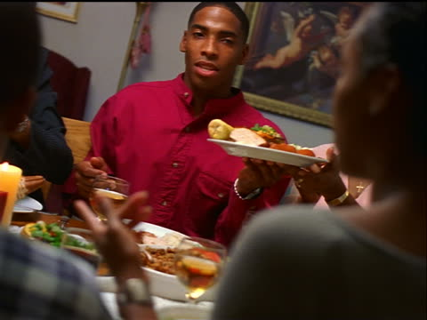 canted dolly shot senior black man serving turkey at holiday table / family passing dish / thanksgiving - thanksgiving stock videos and b-roll footage