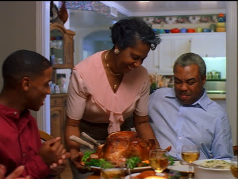dolly shot senior Black woman brings in turkey to holiday table while family claps / Thanksgiving