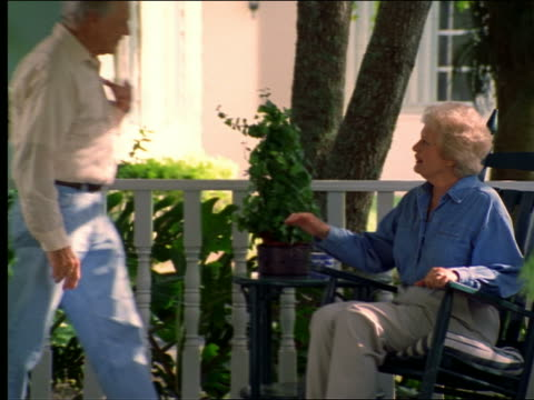 stockvideo's en b-roll-footage met dolly shot senior couple holdings hands + waving off screen from porch - schommelstoel