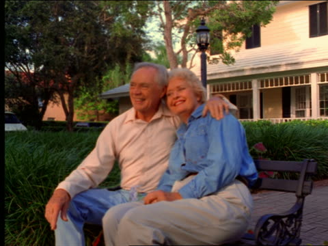 dolly shot senior couple sitting on bench in front of house looking lovingly at each other