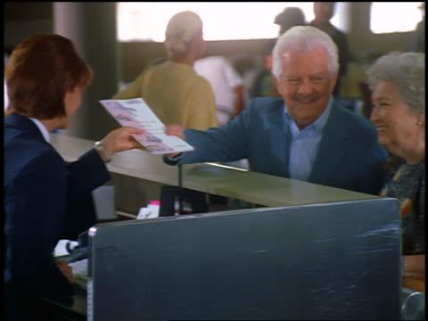 dolly shot senior hispanic couple talking to woman at ticket counter in airport - fahrkarte oder eintrittskarte stock-videos und b-roll-filmmaterial