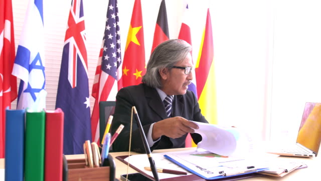 dolly shot side view: dignified and old businessman feel angry while talking colleague on notebook on national flag - bandiera dell'argentina video stock e b–roll