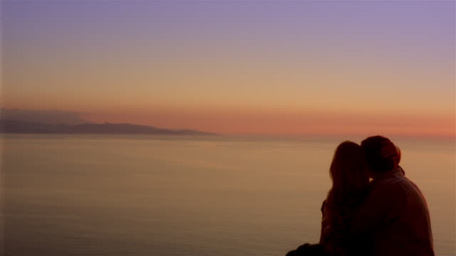Dolly shot silhouette of couple snuggling and looking at sun setting over ocean / Corsica