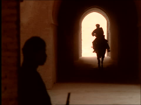 dolly shot silhouette of man riding horse running in arched hallway with 2 men standing guard in foreground / Morocco