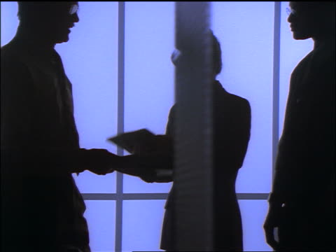 blue dolly shot silhouette two businessmen + businesswoman looking at folders in meeting - femmina con gruppo di maschi video stock e b–roll