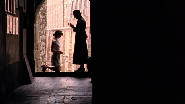 vídeos de stock e filmes b-roll de dolly shot silhouetter profile priest blessing kneeling woman in arched hallway / florence, italy - padre