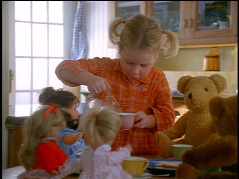 dolly shot small blonde girl pouring milk in teacup for make-believe tea party with dolls - endast flickor bildbanksvideor och videomaterial från bakom kulisserna