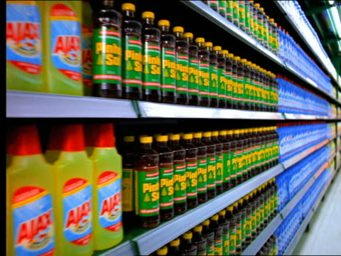 dolly shot supermarket aisle stocked with colorful cleaning supplies