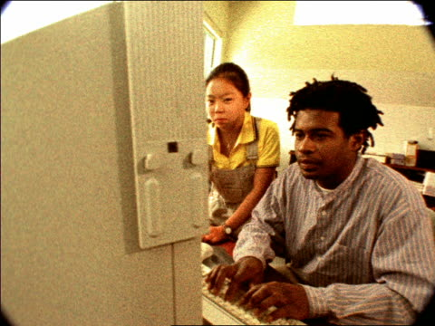 vidéos et rushes de overexposed grainy dolly shot teen asian girl + young black man nodding + pointing at computer - overexposed