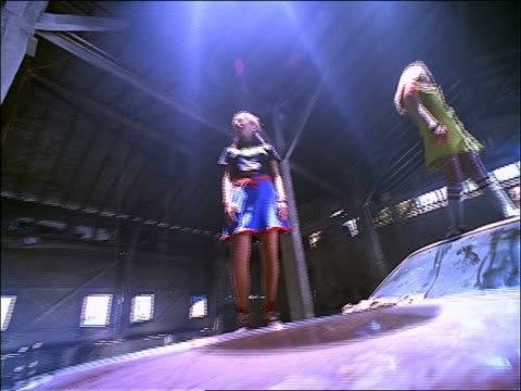 dolly shot three teen girls standing on junked car in old abandoned warehouse - 1997 stock videos & royalty-free footage