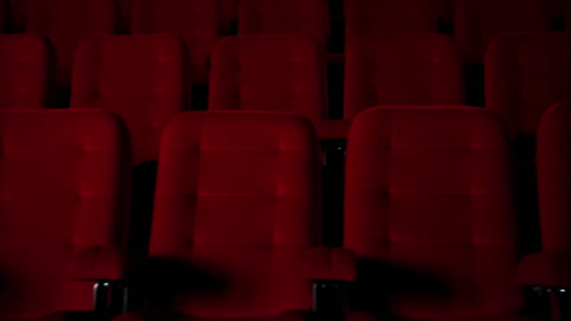 dolly shot through dark empty theater with red seats - seat stock videos & royalty-free footage