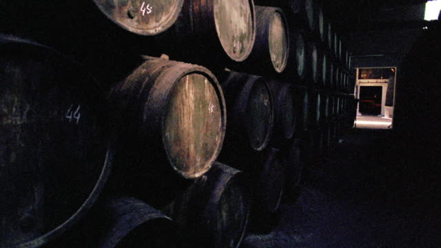 dolly shot pan through two rows of stacked wine barrels in wine cellar / doorway in background / porto, portugal - wine cellar stock videos and b-roll footage
