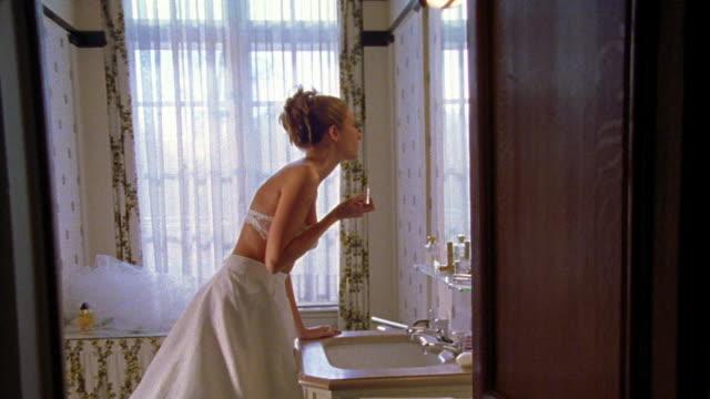 dolly shot thru open door of bathroom toward woman in long white skirt + bra puts on makeup + perfume