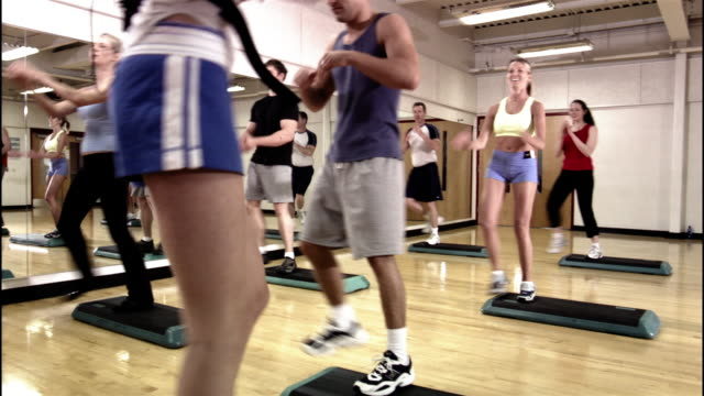 Dolly shot tilt down instructor and students in step aerobics class