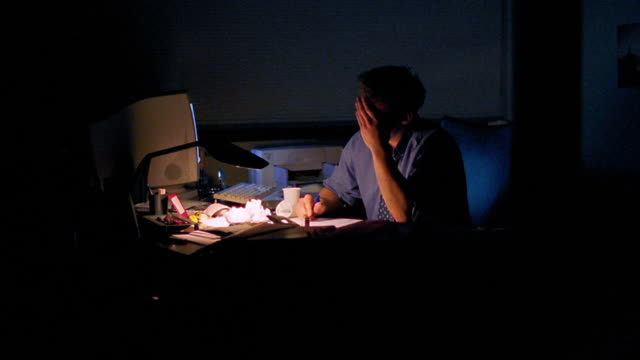 vidéos et rushes de ms dolly shot tired businessman working at desk covered in crumpled papers - crouler sous le travail