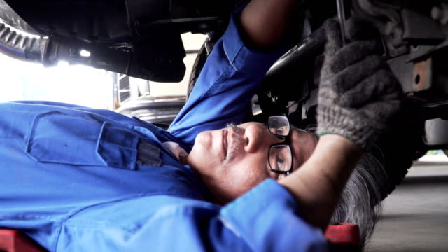 dolly shot to close-up: Asian senior car mechanic move to Under Vehicle from working