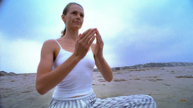 stockvideo's en b-roll-footage met dolly shot to low angle wide shot woman seated in yoga position opening arms on beach / los angeles - noordelijke grote oceaan