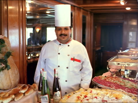 dolly shot to PORTRAIT chubby Egyptian chef in uniform standing behind table piled with food smiling / Egypt