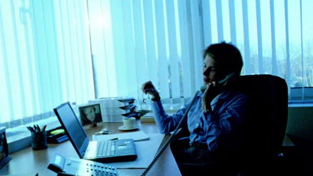 vídeos de stock e filmes b-roll de blue dolly shot toward + away from businesswoman at desk picking up telephone + talking / holding glasses - super exposto