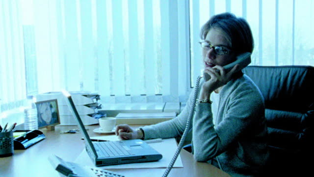 vídeos de stock e filmes b-roll de blue dolly shot toward + away from businesswoman with eyeglasses at desk picking up telephone + talking - super exposto