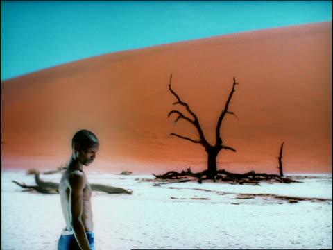 vídeos de stock e filmes b-roll de overexposed dolly shot toward black man standing looking down talking in desert / dead tree in background / africa - super exposto