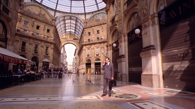 dolly shot toward businessman standing in galleria vittorio emanuele talking on cellular phone / milan - galleria vittorio emanuele ii stock videos and b-roll footage