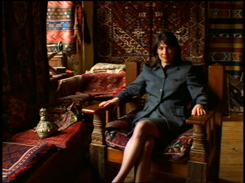 PORTRAIT dolly shot toward businesswoman sitting in chair in Oriental rug store / Istanbul, Turkey