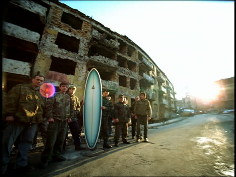 dolly shot toward man holding surfboard in group of men in military fatigues / ruins of bldg in BG/ Sarajevo