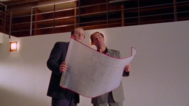 vídeos y material grabado en eventos de stock de dolly shot toward two businessmen standing holding blueprints in empty room, looking at walls + talking - cambio de oficina