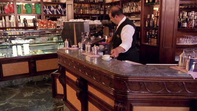 vídeos y material grabado en eventos de stock de dolly shot toward waiter putting coffee cups on counter / waiter with tray passes in foreground / florence - servicio