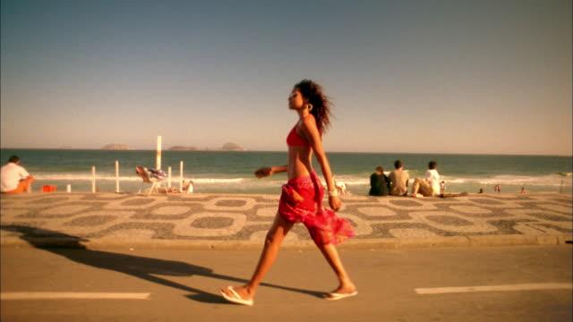 dolly shot tracking shot woman in swimsuit walking on beach boardwalk / rio de janeiro - flip flop stock videos and b-roll footage