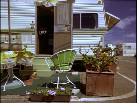 dolly shot trailer home/camper with small dog + patio funiture in front - trailer home stock videos & royalty-free footage
