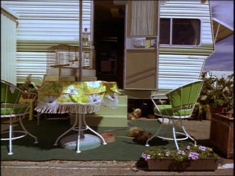 dolly shot trailer home/camper with small dogs (barely visible) + patio funiture in front - trailer home stock videos & royalty-free footage