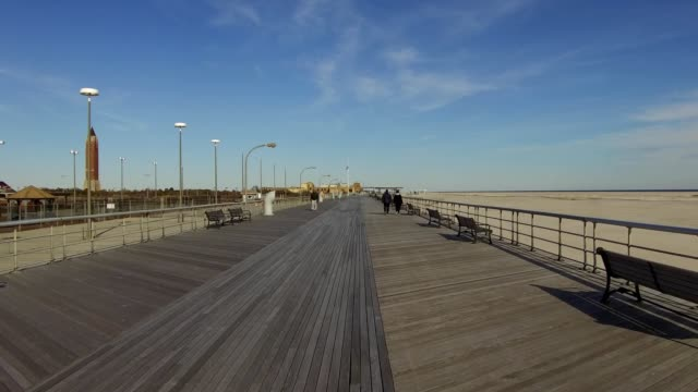 dolly shot traveling down the boardwalk at jones beach on long island, wantagh, new york with iconic water tower and sand visible; visitors walking... - smith tower stock videos & royalty-free footage