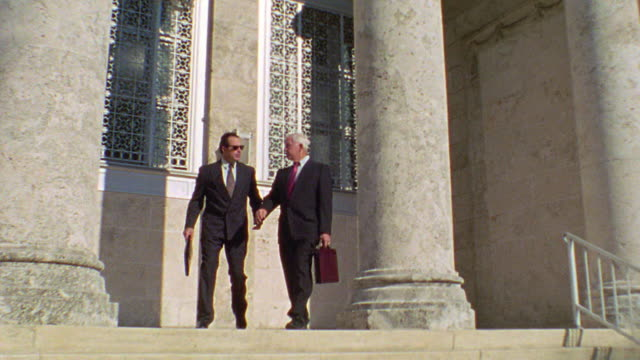 dolly shot two businessmen/lawyers carrying briefcases walking down stairs outside of courthouse